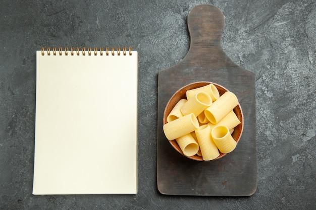 Widok z góry surowego włoskiego makaronu trochę utworzonego na szarym tle żywności surowego mączki makaronu ciasta