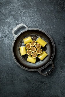 Widok z góry surowego włoskiego makaronu z mięsem wewnątrz patelni na ciemnym tle mączka surowego ciasta makaron żywności