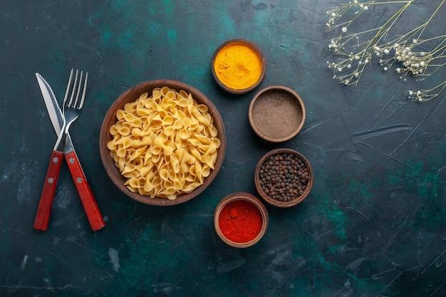 Widok z góry surowego włoskiego makaronu z przyprawami na ciemnoniebieskim biurku składnik żywności posiłek surowy