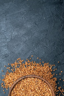 Widok z góry surowej gryki wewnątrz brązowego talerza na szarej przestrzeni