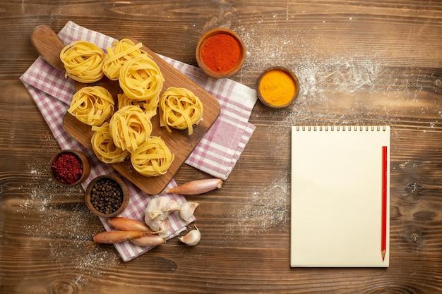Widok z góry surowy kwiat ciasta uformowany makaron z przyprawami na brązowym tle mączka ciasta makaron spożywczy