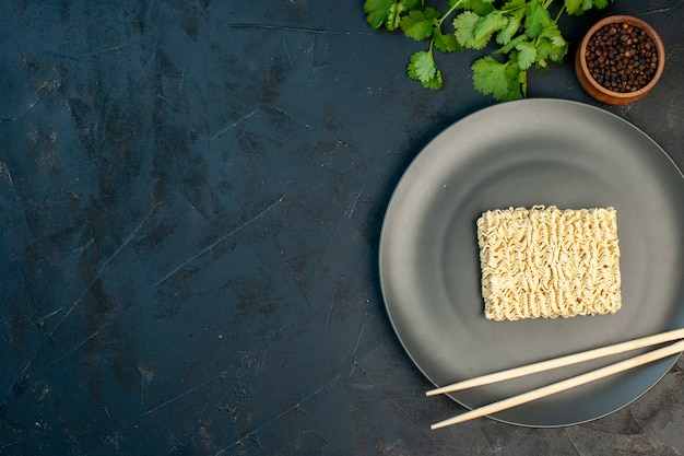 Widok z góry surowy makaron wewnątrz talerza z patyczkami na ciemnoniebieskim miejscu wolnym od ściany