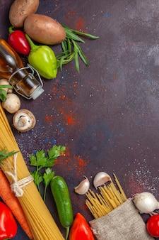 Widok z góry surowy makaron ze świeżymi warzywami na ciemnej powierzchni posiłek sałatkowy jedzenie