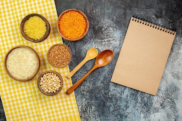 Widok z góry surowy ryż z makaronem i surową kaszą gryczaną w małych doniczkach na jasnoszarym stole