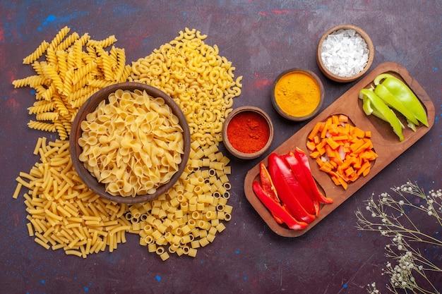 Widok z góry surowy włoski makaron inny uformowany mały makaron z pokrojoną papryką na ciemnej powierzchni jedzenie surowy włoski makaron posiłek kolor