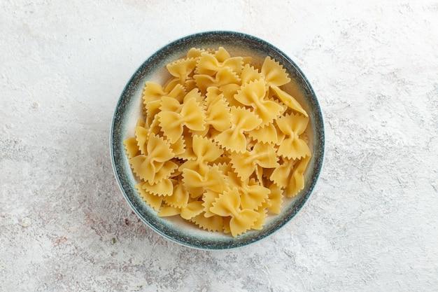 Widok z góry surowy włoski makaron mało utworzony na białej powierzchni włoski makaron posiłek jedzenie ciasto warzywne