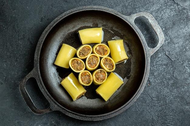 Widok z góry surowy włoski makaron z mięsem wewnątrz patelni iz zielenią na ciemnym tle mąka z ciasta makaronowego