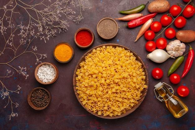 Widok z góry surowy włoski makaron z różnymi przyprawami i świeżymi warzywami na ciemnym tle składnik produktu posiłek żywność warzywo