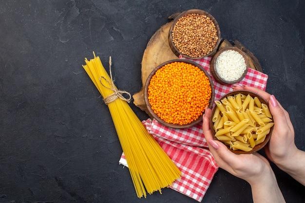 Widok z góry surowy włoski makaron z soczewicą i kaszą gryczaną na ciemnym tle jedzenie obiad posiłek kolor gotowanie kuchnia makaron ciasto ciemność