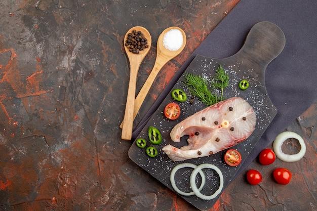 Widok z góry surowych ryb i papryki, cebuli, zielonych pomidorów na czarnej desce do krojenia na ciemnym ręczniku po lewej stronie na powierzchni o mieszanym kolorze