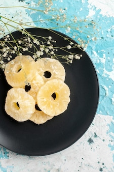 Widok z góry suszone krążki ananasa wewnątrz talerza na niebieskiej powierzchni owoce ananas suchy słodki cukier