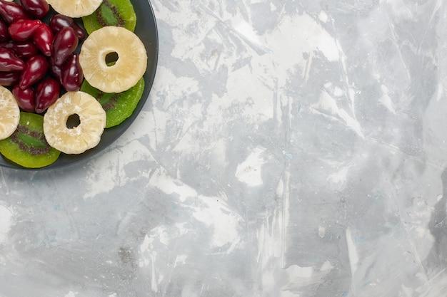 Widok z góry suszone owoce pierścienie ananasa i plasterki kiwi na jasnym białym tle owoce suchy słodki cukier kwaśny