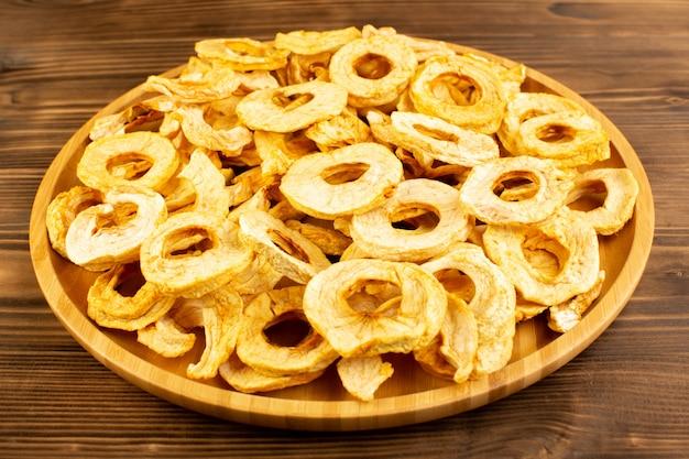 Widok z góry suszone pierścienie ananasa wewnątrz płytki suszone owoce kwaśny smaczny niepowtarzalny smak na brązowym drewnianym biurku owoce egzotyczne wytrawne