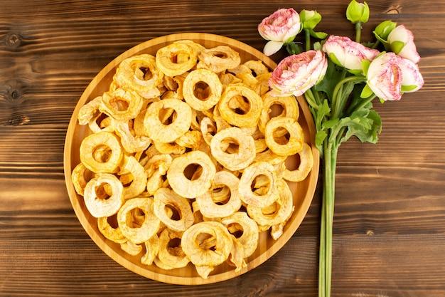 Widok z góry suszone pierścienie ananasa wewnątrz płyty suszone owoce kwaśny smaczny niepowtarzalny smak wraz z różowymi kwiatami na brązowym drewnianym biurku owoce egzotyczne wytrawne