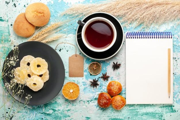 Widok z góry suszone pierścienie ananasa z filiżanką herbaty i plików cookie na niebieskim tle ciasto bake owocowe herbatniki słodkie ciasteczka cukru