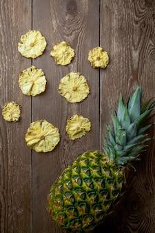 Widok z góry suszonego ananasa i świeżego ananasa na drewnianym stole