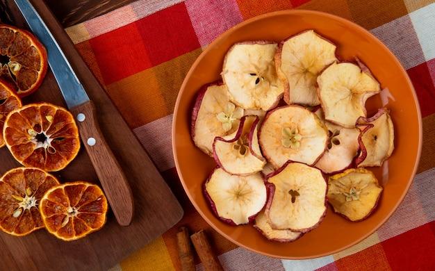 Widok z góry suszonych plasterków pomarańczy z kuchennym nożem na drewnianej desce do krojenia i suszonych plasterków jabłka na talerzu na kraciastym obrusie