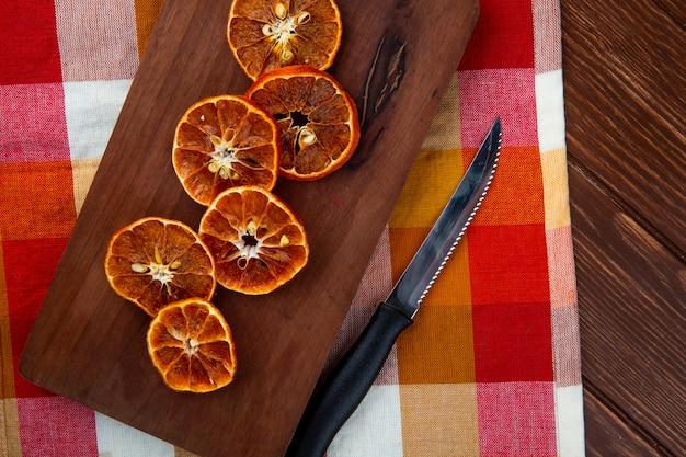 Widok z góry suszonych plasterków pomarańczy z kuchennym nożem na drewnianej desce do krojenia na kraciastym obrusie