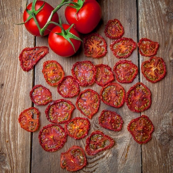 Widok z góry suszonych pomidorów i świeżych pomidorów na drewnianym stole