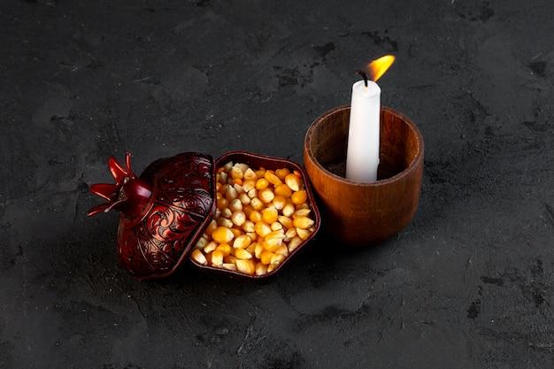 Widok z góry suszonych ziaren kukurydzy w filiżance z płonącą świecą