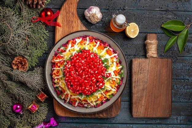 Widok z góry świąteczne jedzenie na desce świąteczne danie na desce obok kuchni deska butelka olejku gałązki z szyszkami miska przypraw czosnek cytryna