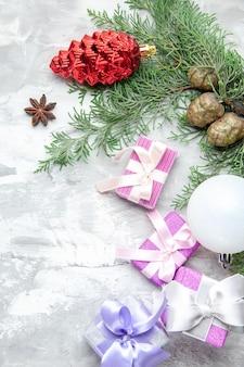 Widok z góry świąteczne prezenty świąteczne zabawki choinkowe gałęzie sosny na szarym tle