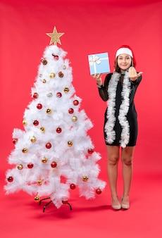 Widok z góry świątecznego nastroju z piękną dziewczyną w czarnej sukience z czapką świętego mikołaja stojącą w pobliżu choinki