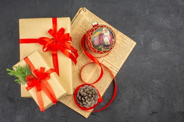 Widok z góry świąteczny prezent w brązowej papierowej wstążce choinka zabawka na gazecie na ciemnej powierzchni