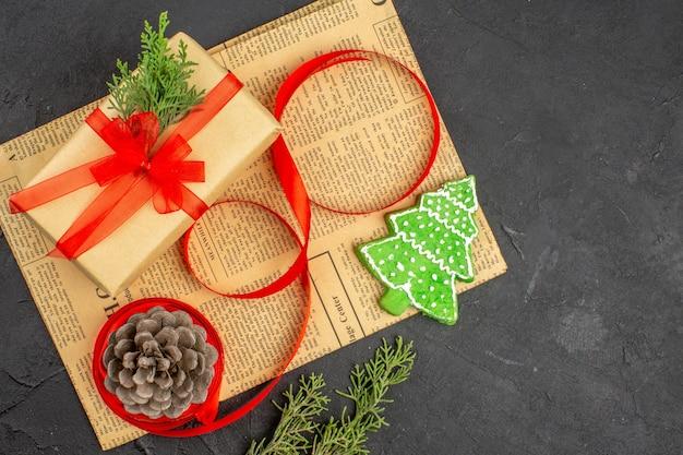 Widok z góry świąteczny prezent w brązowej wstążce jodłowej gałęzi na gazetowych ozdobach świątecznych na ciemnej powierzchni