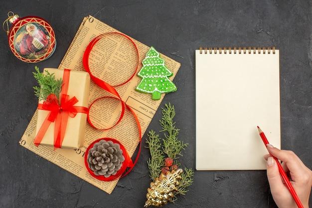 Widok z góry świąteczny prezent w brązowej wstążce jodłowej gałęzi papieru na gazetach ozdoby świąteczne notatnik ołówek w kobiecej dłoni na ciemnej powierzchni