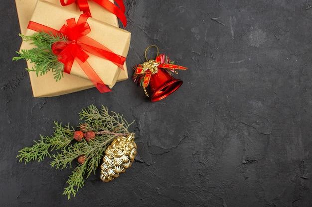 Widok z góry świąteczny prezent w brązowym papierze związany z czerwoną wstążką ozdoby choinkowe na ciemnej powierzchni