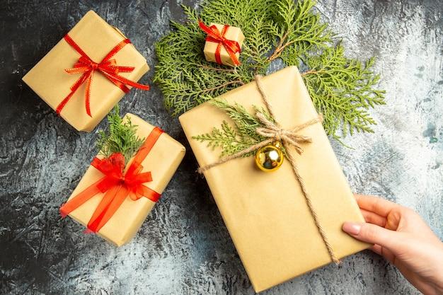 Widok z góry świąteczny prezent w kobiecej dłoni małe prezenty gałęzie sosny na szarej powierzchni