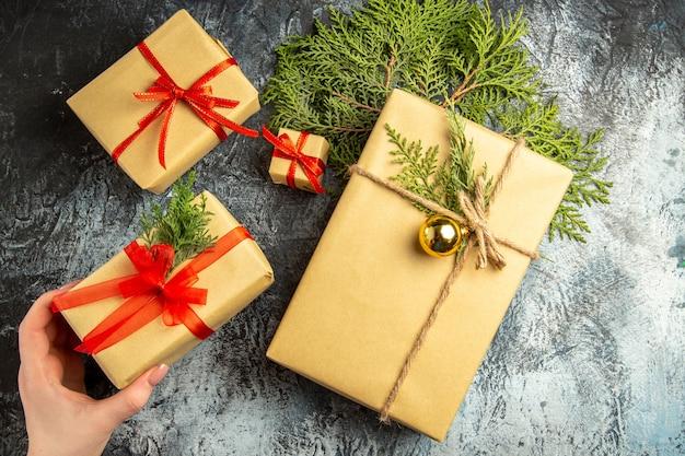 Widok z góry świąteczny prezent w ręce kobiety małe prezenty gałęzie sosny na szarej powierzchni