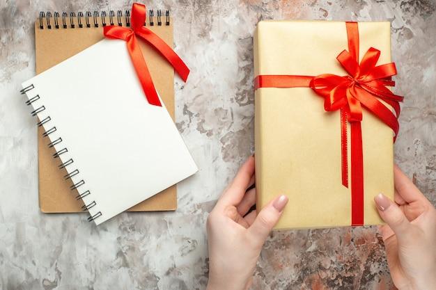 Widok z góry świąteczny prezent związany z czerwoną kokardą na białym noworoczny prezent zdjęcie świąteczny kolor bożego narodzenia