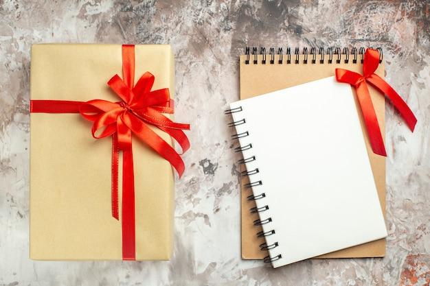Widok z góry świąteczny prezent związany z notatnikiem z czerwoną kokardą na białym zdjęciu świąteczny kolor prezent na nowy rok boże narodzenie