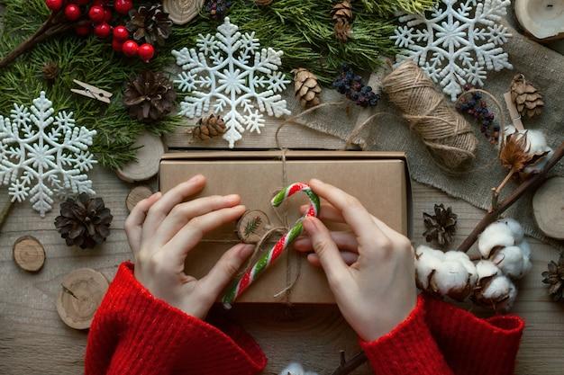 Widok z góry. świąteczny wystrój. kobiece dłonie w czerwonym swetrze zdobią pudełko ze słodyczami. w pobliżu leżą gałęzie, płatki śniegu, bawełna, szyszki, czerwone jagody, drewniane domki z bali.