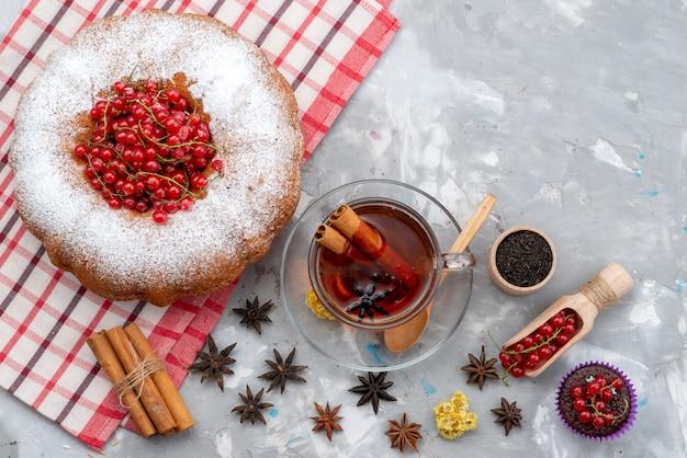 Widok z góry świeża czerwona żurawina kwaśna i łagodna z herbatą okrągłego ciasta i cynamonem na białym tle o świeżym kolorze