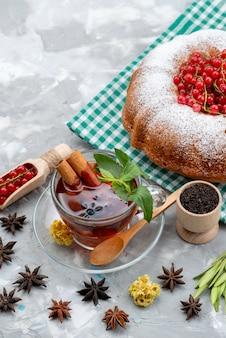 Widok z góry świeża czerwona żurawina kwaśna i łagodna z okrągłym ciastem, herbatą i cynamonem na białym biurku jagody owocowe