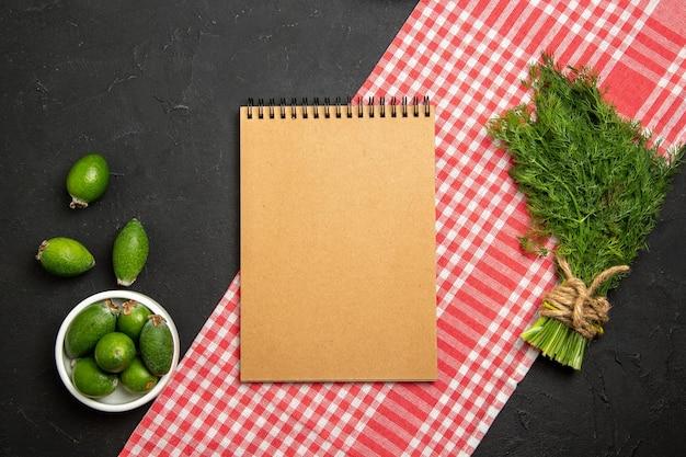 Widok z góry świeża feijoa z zieleniną i notatnikiem na ciemnej powierzchni zielony owocowy świeży zielony