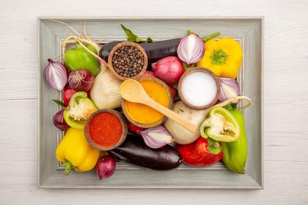Widok z góry świeża kompozycja warzywna z przyprawami na białym stole