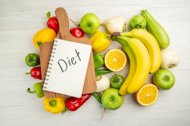 Widok z góry świeża papryka z bananami i pomarańczą na białym tle sałatka zdrowe życie zdjęcie dojrzałe kolory