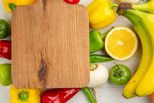 Widok z góry świeża papryka z bananami i pomarańczą na białym tle sałatka zdrowe życie zdjęcie kolor dieta