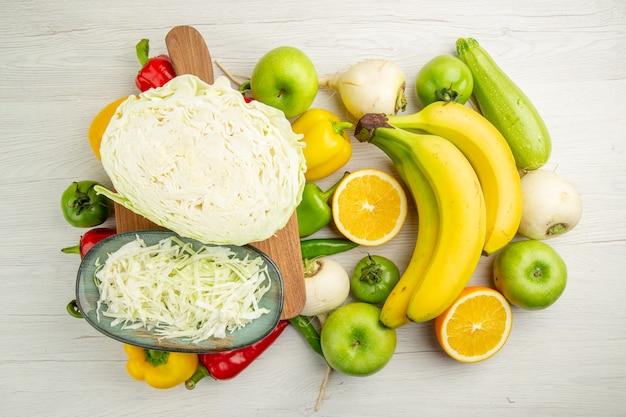 Widok z góry świeża papryka z bananami kapustą i jabłkami na białym tle sałatka ze zdjęć zdrowe życie dojrzała dieta kolor
