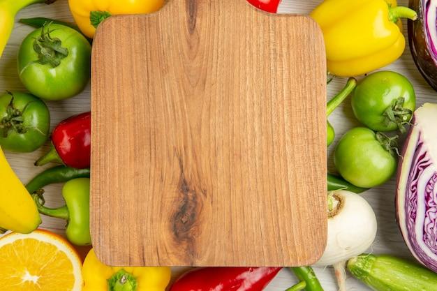 Widok z góry świeża papryka z jabłkami, bananami i czerwoną kapustą na białym tle dojrzały kolor zdrowe życie dieta sałatka
