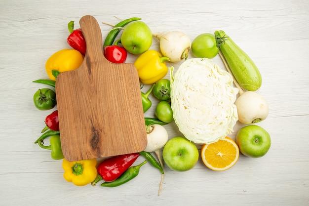 Widok z góry świeża papryka z jabłkami i kapustą na białym tle kolorowa sałatka ze zdjęciami zdrowe życie dojrzała dieta