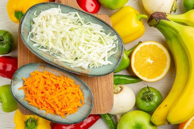 Widok z góry świeża papryka z pokrojonymi w plasterki kapustą bananami, jabłkami i pomarańczą na białym tle sałatka ze zdjęć zdrowe życie dojrzała dieta kolor