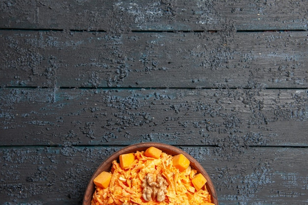 Widok z góry świeża sałatka z marchwi tarta sałatka z orzechami włoskimi i czosnkiem na ciemnym biurku dieta dojrzała kolorowa sałatka zdrowie
