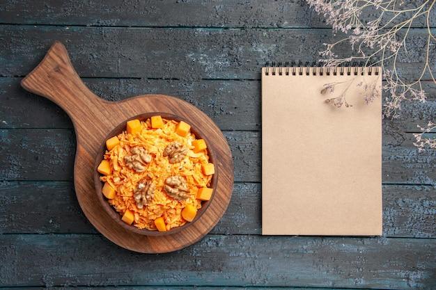 Widok z góry świeża sałatka z marchwi tarta sałatka z orzechami włoskimi na ciemnym biurku kolor orzechów sałatka dietetyczna zdrowa