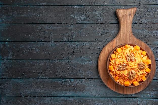 Widok z góry świeża sałatka z marchwi tarta sałatka z orzechami włoskimi na ciemnym biurku sałatka dietetyczna kolor orzechów zdrowie