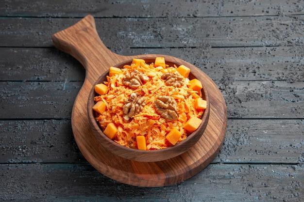 Widok z góry świeża sałatka z marchwi tarta sałatka z orzechami włoskimi na ciemnym biurku sałatka kolor orzechów dieta zdrowotna